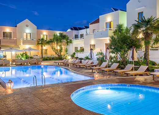 Two separate pools and the exterior of Oscar Suites & Village hotel at night.
