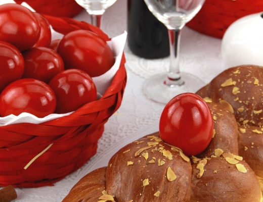 Red eggs in a basket and a traditional sweet on a table at Easter in Crete.