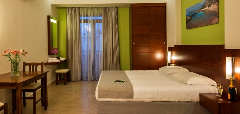 Bed, table and wardrobe by the window in Oscar Suites & Village in Platanias, Crete.