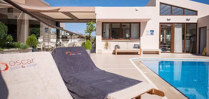 Oscar Suites & Village towels on comfortable sunbeds by the swimming pool.