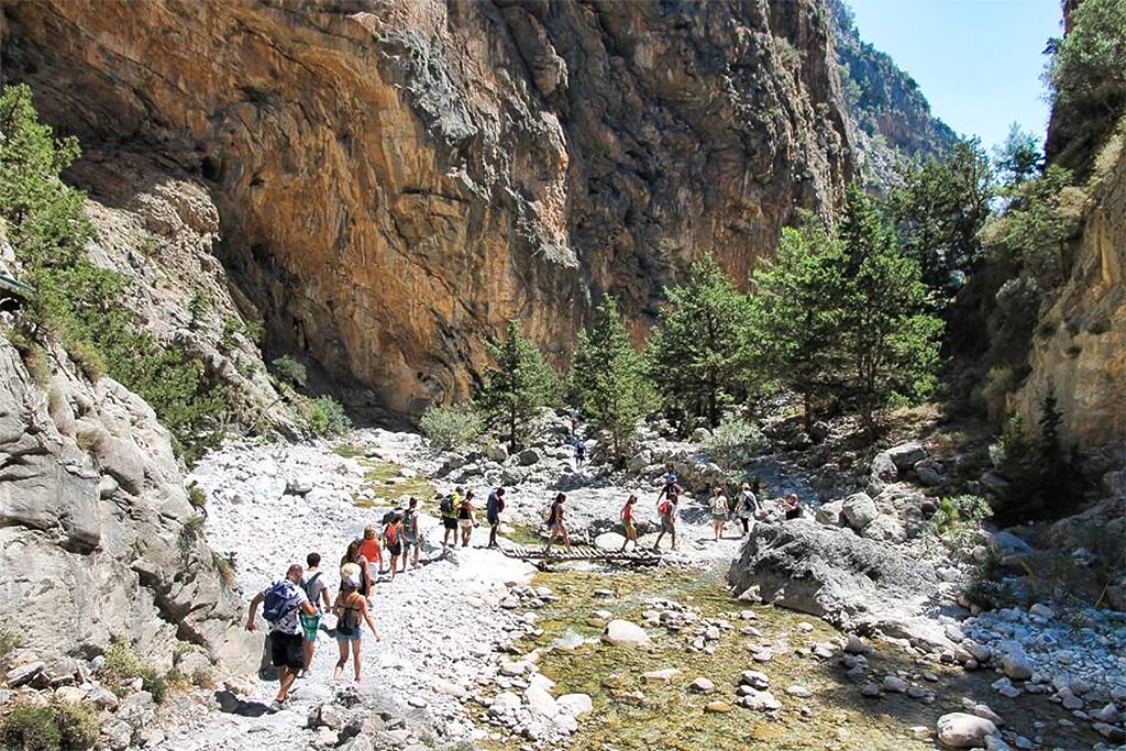 Tourists walking along Samaria Gorge in Chania, Crete, where Oscar Suites & Village is located.