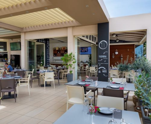 Dining tables and chairs in the Valentino Pasta & Grill restaurant in Oscar Suites & Village.