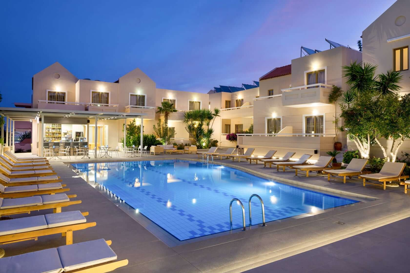Sun beds by the swimming pool at dusk in Oscar Suites & Village in Agia Marina Chania.