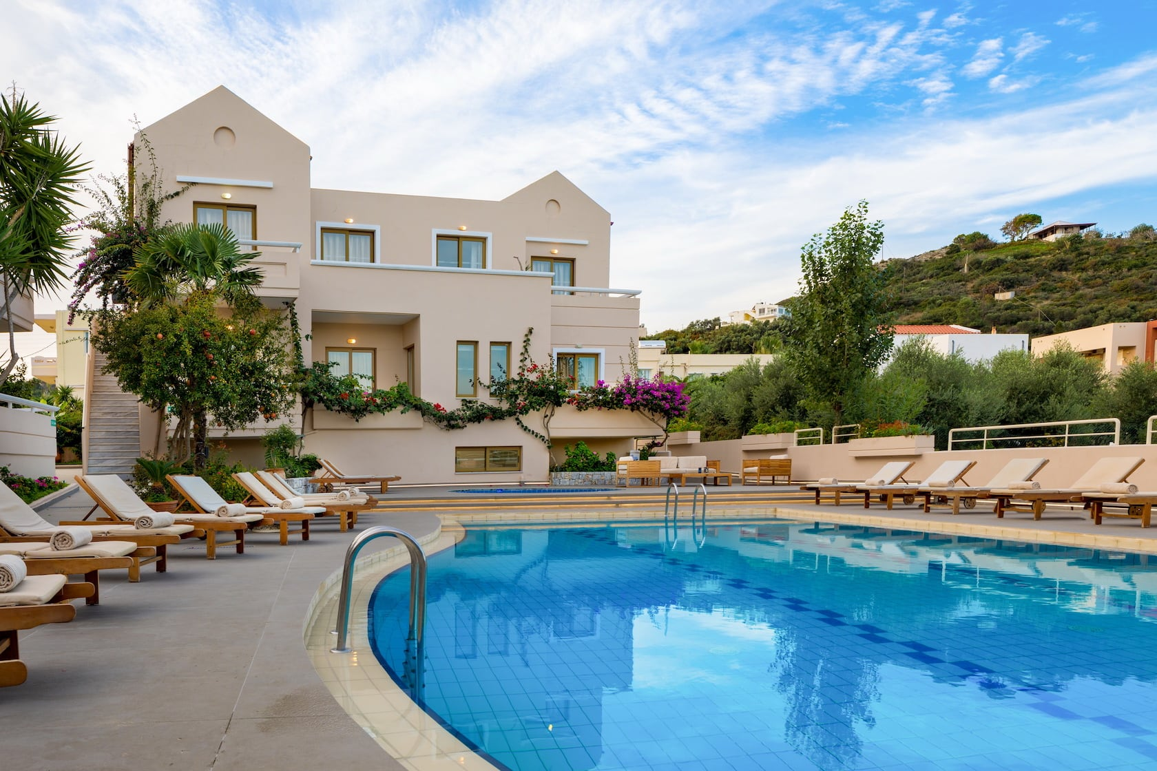 Sunbeds by the crystal clear swimming pool in Oscar Suites & Village in Chania, Crete.