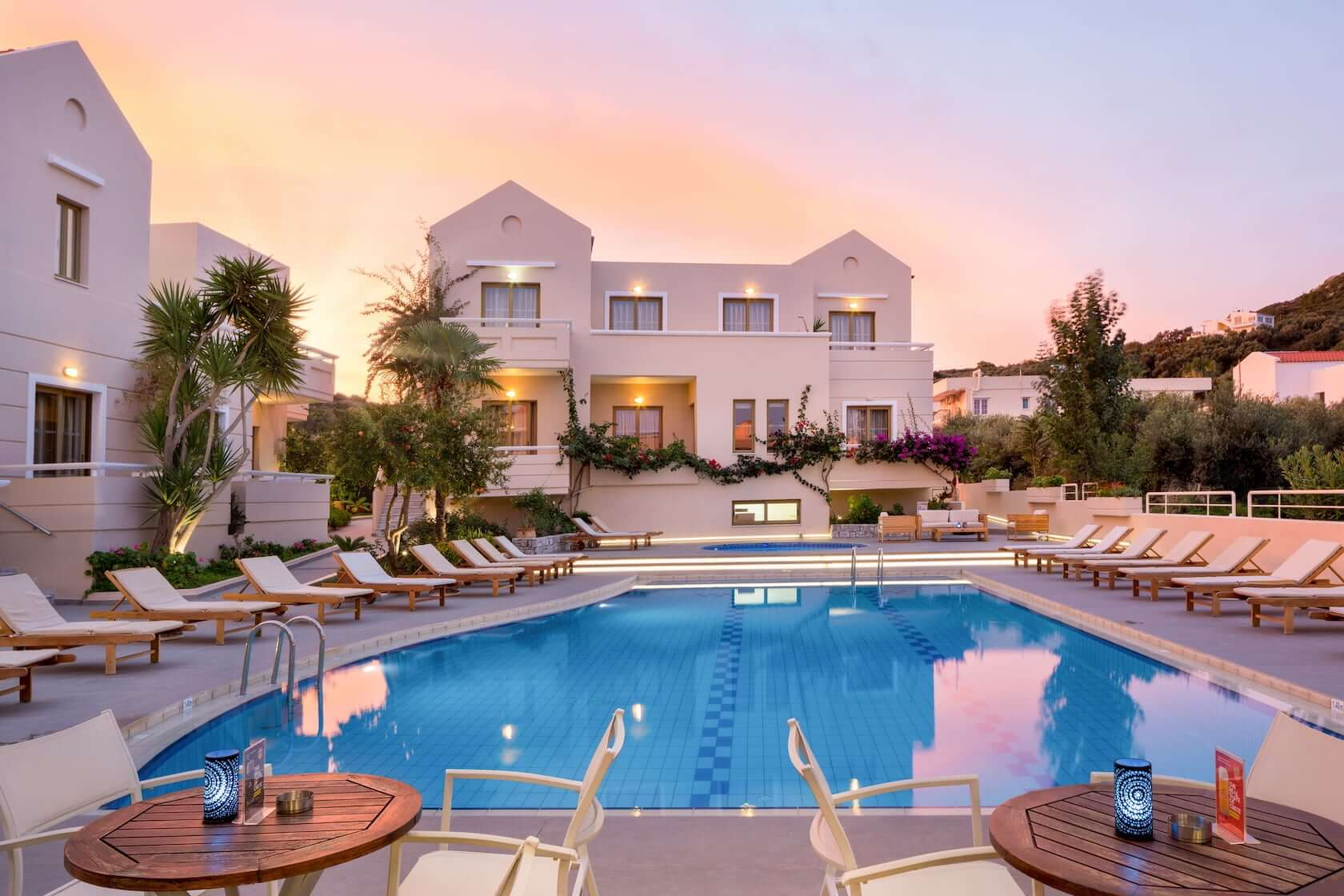 Dusk at Oscar Suites & Village hotel in Agia Marina Chania. Sun loungers by the pool.