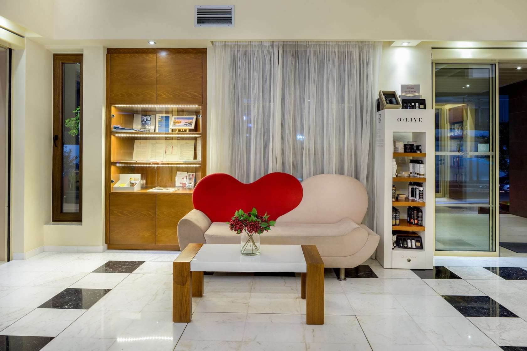 Sofa with heart-shaped back and a little table in the reception area in Oscar Suites & Village.