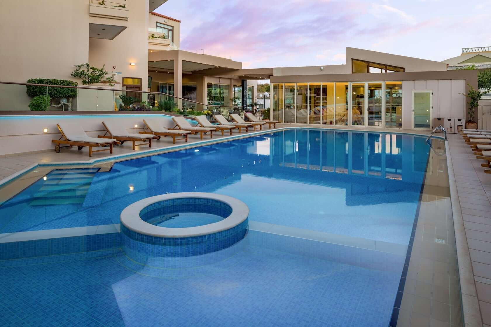 Sunbeds by the sizeable swimming pool in Oscar Suites & Village in Agia Marina Platanias, Crete.