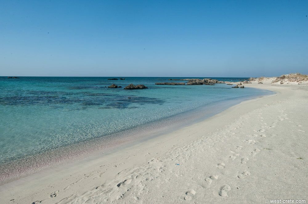 Crystal clear sea and footsteps on the sand at a beach in Chania, Crete.