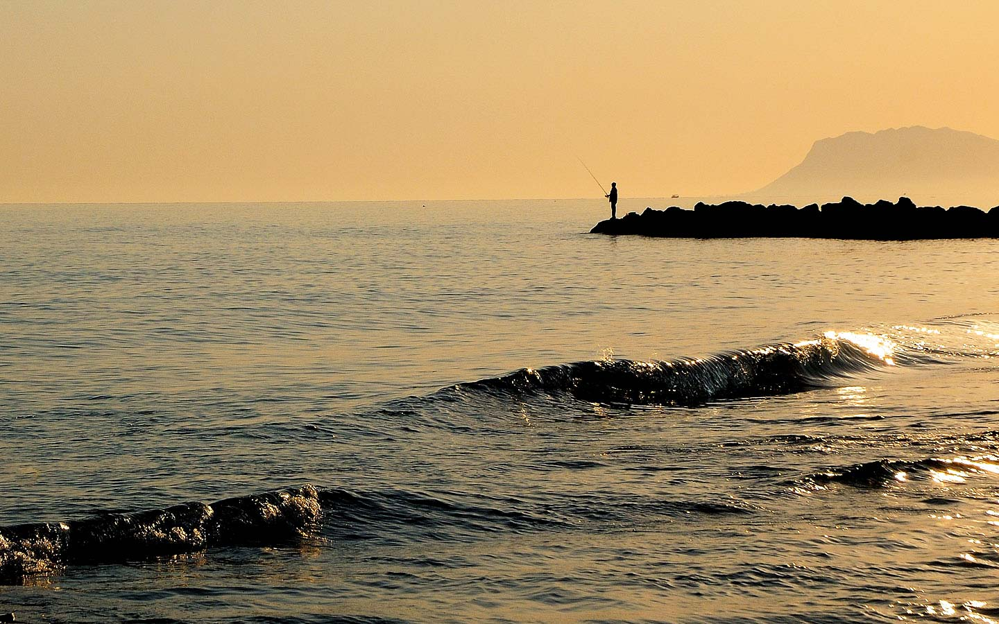 Man sea fishes on the coast of Crete, home of Oscar Suites & Village hotel in Agia Marina Platanias