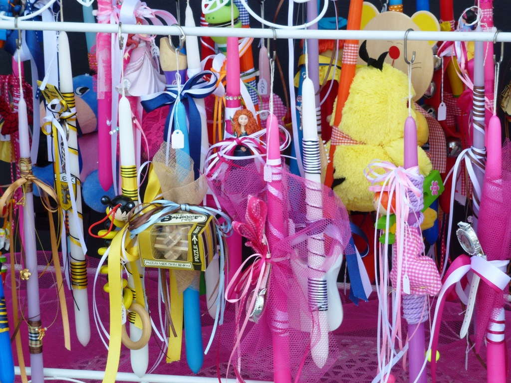 Easter candles with yellow, pink and blue ribbons in a store in Chania, Crete.