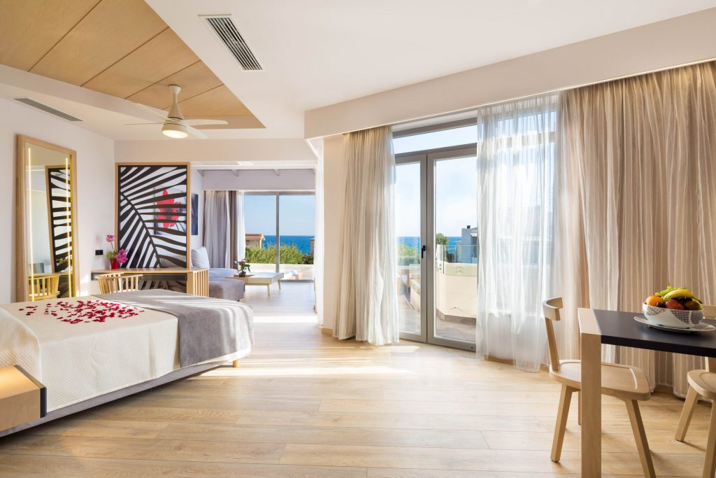 Spacious bedroom with double bed and wide windows in Sea View Suite in Oscar Suites & Village.