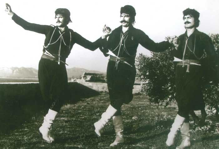 Three Cretans wearing traditional clothes dancing Cretan dances.