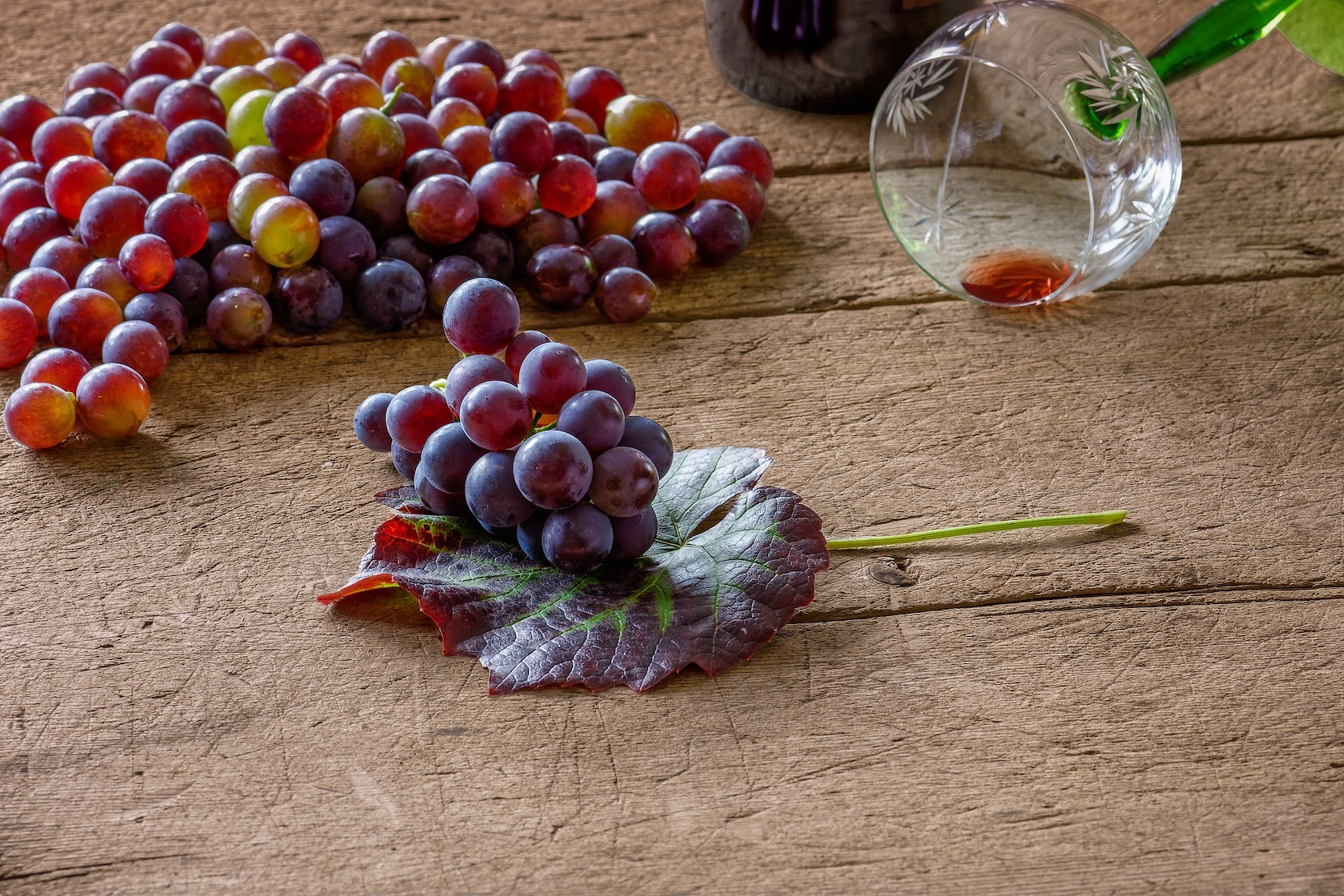 Red grapes on a wooden table. Guests can sample wine from the Cretan vineyard.